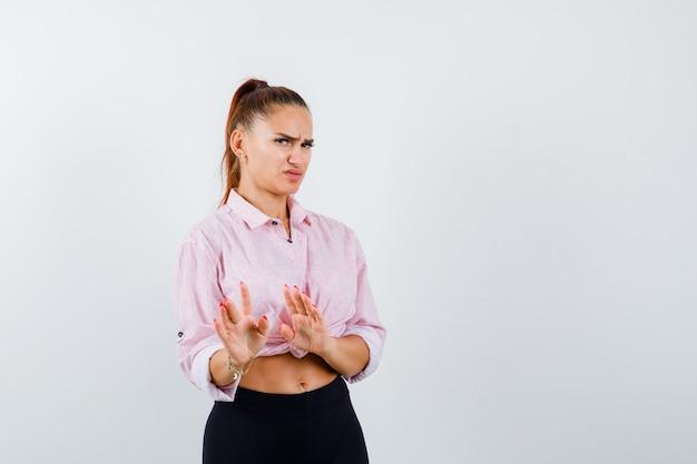 Jeune femme montrant des paumes dans le geste d'abandon en chemise décontractée et à la mécontentement, vue de face.