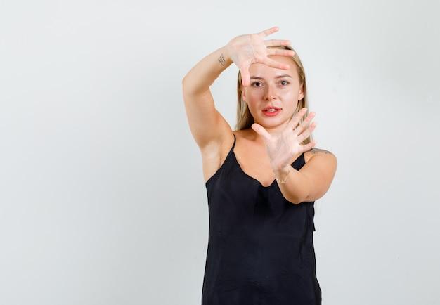 Jeune femme montrant les paumes ouvertes des mains en maillot noir