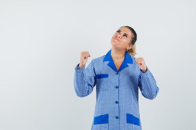 Jeune femme montrant la pose du gagnant et regardant au-dessus en chemise de pyjama vichy bleu et à la joyeuse vue de face.