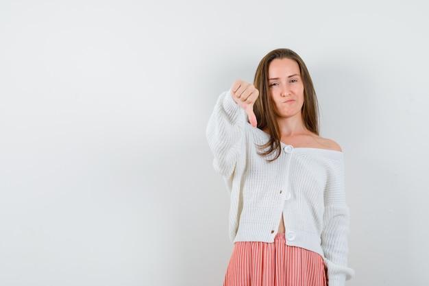 Jeune femme montrant le pouce vers le bas en cardigan et jupe à l'isolement mécontent