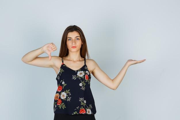 Jeune femme montrant le pouce vers le bas, propagation de la paume en haut floral et à la colère