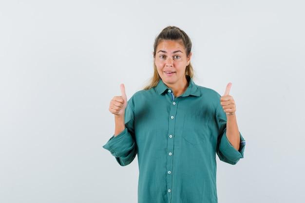 Jeune femme montrant le pouce vers le haut en chemise bleue et à la joie