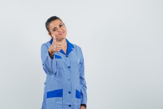 Jeune femme montrant le pouce vers le haut en chemise de pyjama vichy bleu et à la jolie. vue de face.