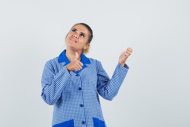 Jeune femme montrant le pouce vers le haut et levant la main en chemise de pyjama vichy bleu et à la jolie. vue de face.