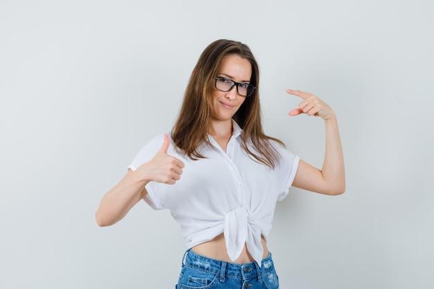 Jeune femme montrant le pouce vers le haut, pointant ses lunettes en chemisier blanc, lunettes vue de face.