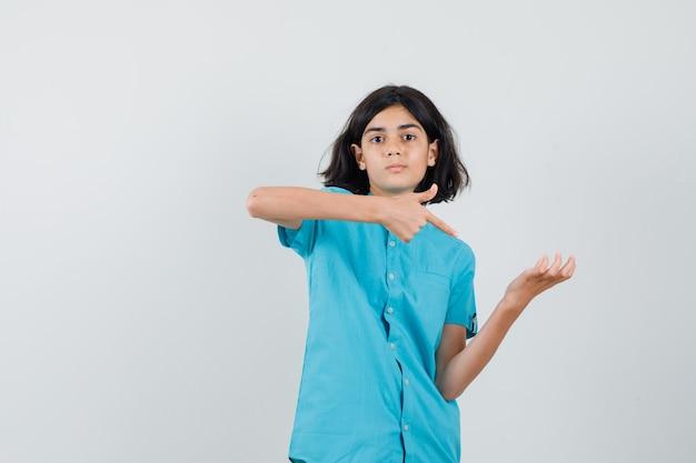 Jeune femme montrant le pouce vers le haut tout en levant sa paume ouverte en chemise bleue et en regardant grand.