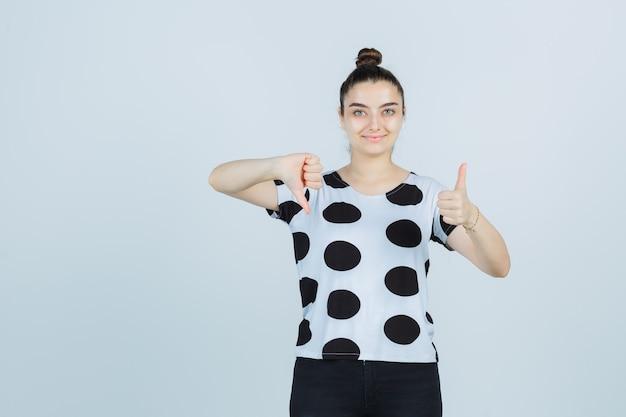 Jeune femme montrant les pouces de haut en bas en t-shirt, jeans et à la béatitude. vue de face.