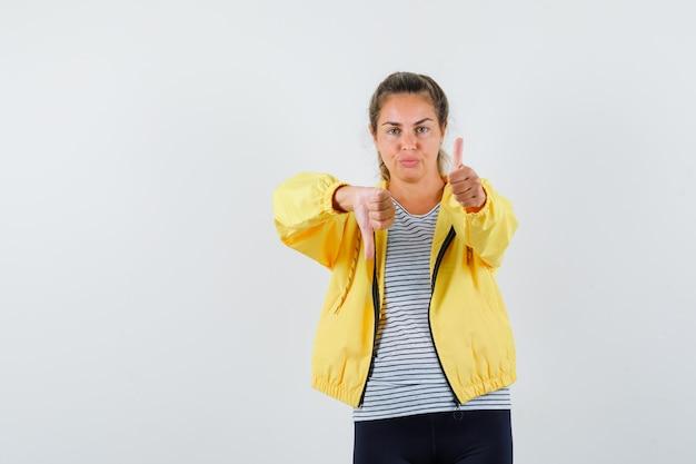 Jeune femme montrant les pouces de haut en bas en veste, t-shirt et à la confiance. vue de face.