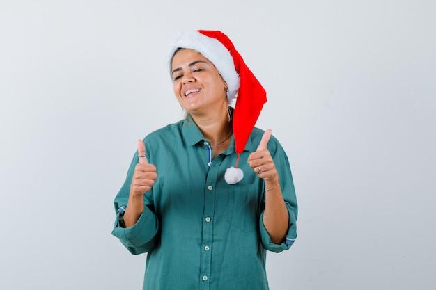 Jeune femme montrant les pouces vers le haut en chemise, bonnet de noel et l'air satisfait, vue de face.