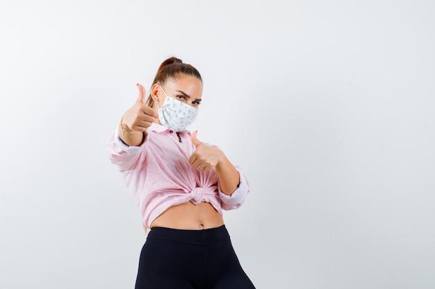 Jeune femme montrant les pouces vers le haut en chemise, pantalon, masque médical et à la vue de face, confiant.