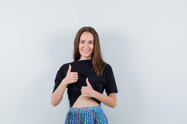 Jeune femme montrant les pouces vers le haut avec les deux mains en t-shirt noir et jupe bleue et à la radieuse