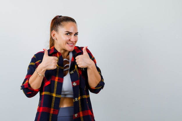 Jeune femme montrant les pouces vers le haut en haut court, chemise à carreaux et l'air heureux. vue de face.