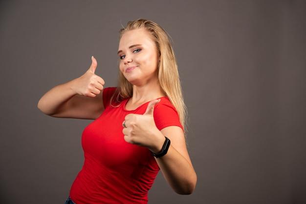 Jeune femme montrant les pouces vers le haut sur un mur sombre.