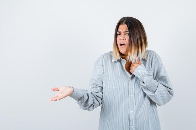 Jeune femme montrant quelque chose en chemise surdimensionnée et à la perplexité. vue de face.