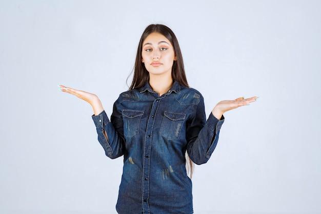 Jeune femme montrant quelque chose dans sa main ouverte