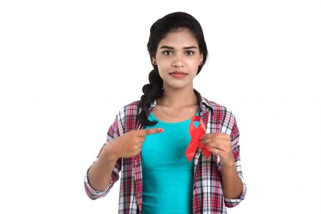 Jeune femme montrant un ruban rouge vih, ruban de sensibilisation au sida, concept de soins de santé et médecine