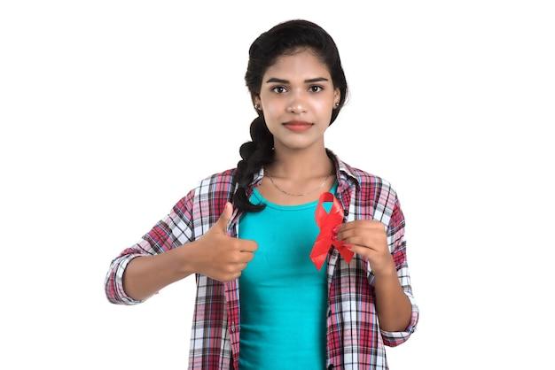 Jeune femme montrant le ruban rouge vih, ruban de sensibilisation au sida, concept de soins de santé et de médecine