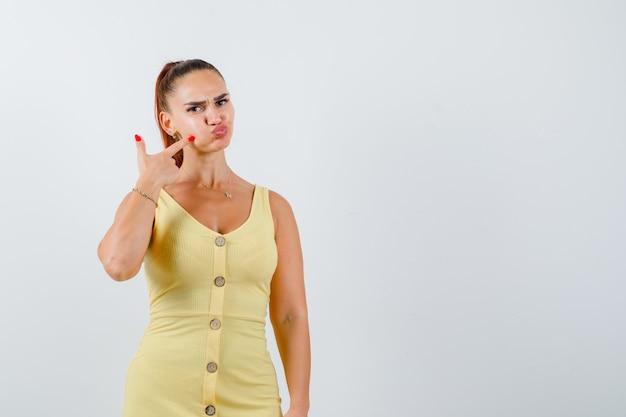Jeune femme montrant sa joue gonflée en robe jaune et à la drôle. vue de face.