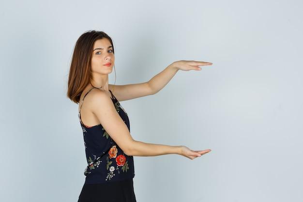 Jeune femme montrant un signe de grande taille en blouse, jupe et l'air confiant. .