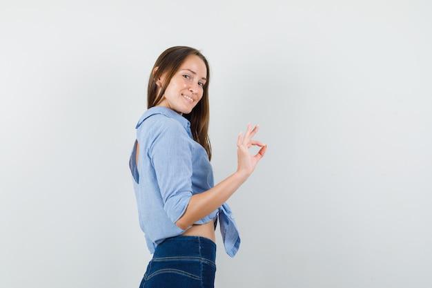 Jeune femme montrant signe ok en chemise bleue, pantalon et à la joyeuse.