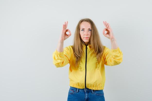 Jeune femme montrant le signe ok avec les deux mains en blouson aviateur jaune et bleu jean et à la recherche de sérieux. vue de face.