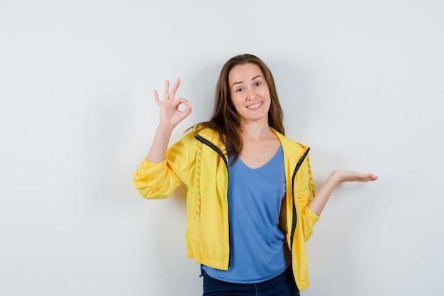 Jeune femme montrant un signe ok, écartant la paume en t-shirt, veste et semblant joyeuse, vue de face.