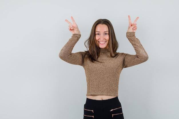 Jeune femme montrant le signe de la paix avec les deux mains en pull doré et pantalon noir et à heureux