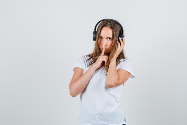Jeune femme montrant le signe de silence avec la main sur les écouteurs en t-shirt blanc