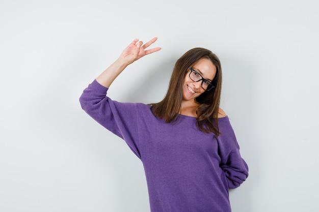 Jeune femme montrant le signe de la victoire en chemise violette et à la joyeuse vue de face.