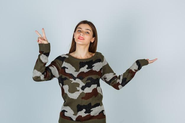 Jeune femme montrant le signe de la victoire en faisant semblant de montrer quelque chose en pull