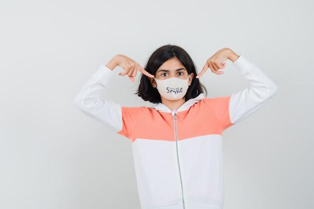 Jeune femme montrant son masque à capuche, masque facial.