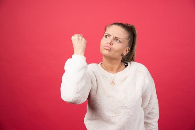 Jeune femme montrant son poing sur un mur rouge