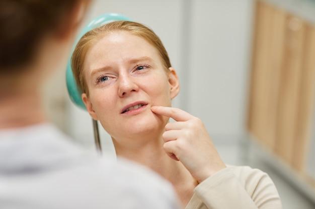 Jeune femme montrant son visage et se plaignant de maux de dents au dentiste lors de sa visite
