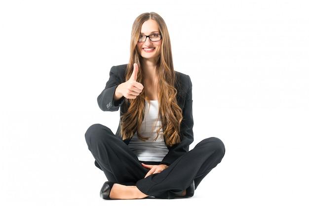Jeune femme montrant le succès assis en tailleur