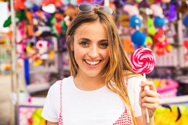 Jeune femme montrant une sucette rouge