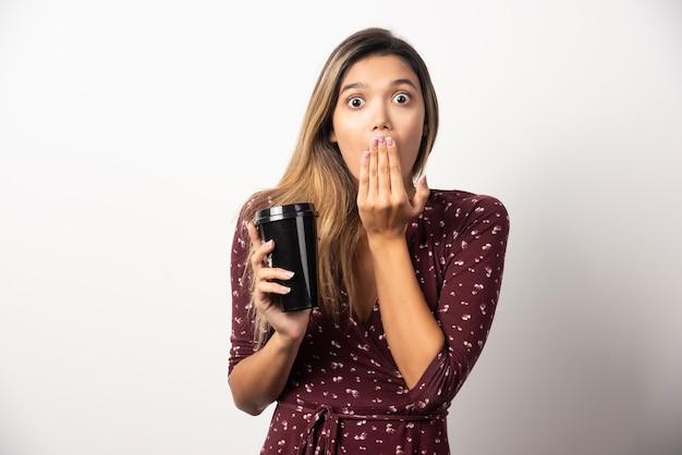 Jeune femme montrant une tasse de boisson sur un mur blanc.