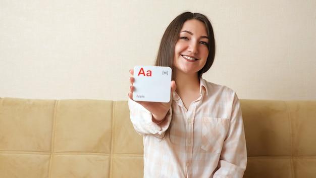 Une jeune femme montre des cartes avec des lettres de l'alphabet anglais et prononce des sons et des mots