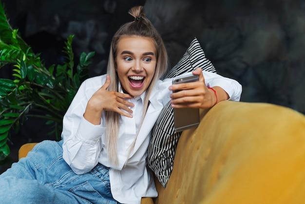 Jeune femme montre des émotions positives lumineuses lors de la communication