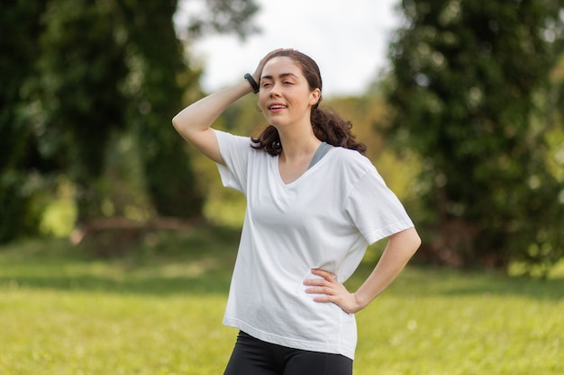 Une jeune femme avec une montre intelligente sur les mains se détend après l'échauffement dans le parc. le concept d'un appareil moderne et bien-être