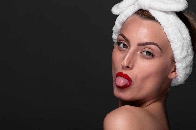 Jeune femme montre sa langue