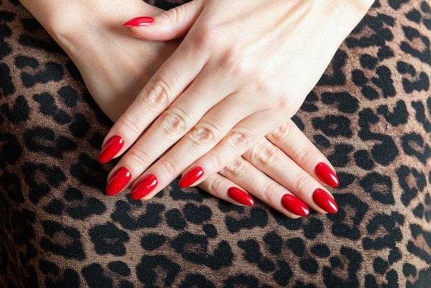 Jeune femme montre ses ongles manucure rouge