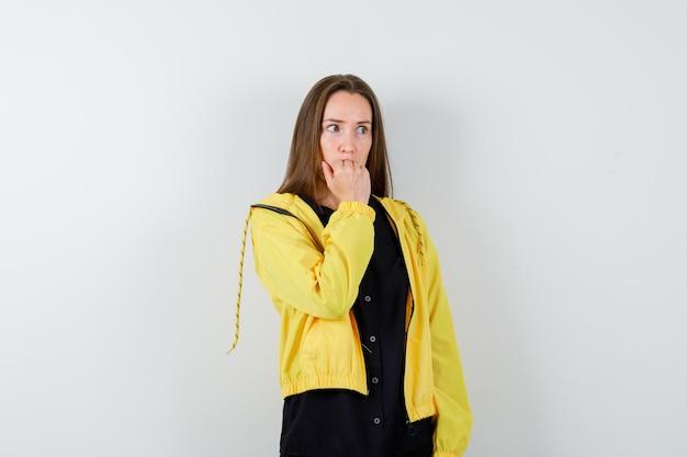 Jeune femme mordant le poing et semblant anxieuse