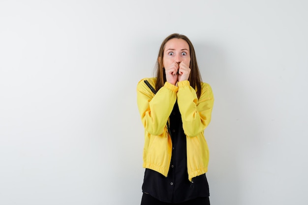 Jeune femme mordant les poings et semblant anxieuse