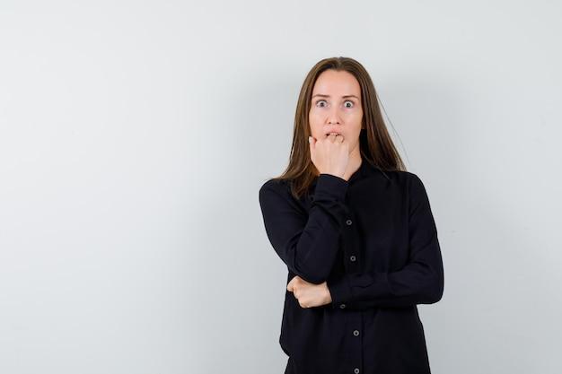 Jeune femme mordre le poing et à la surprise