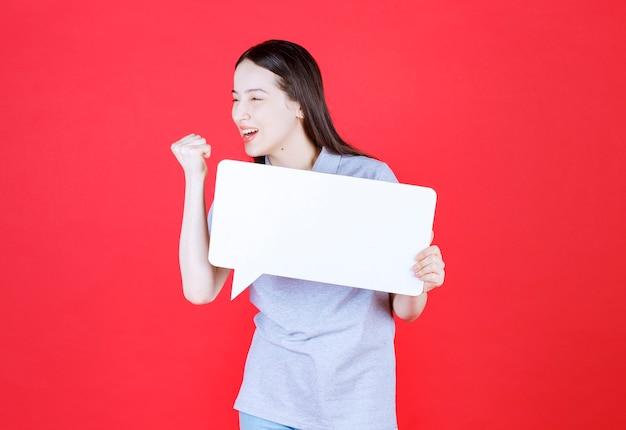 Jeune femme motivée tenant le conseil et serrez son poing