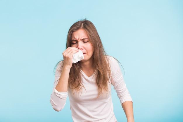 Jeune femme avec mouchoir, a le nez qui coule sur le mur bleu