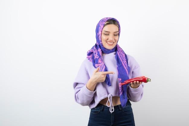 Jeune femme en mouchoir pointant sur un poivron rouge.