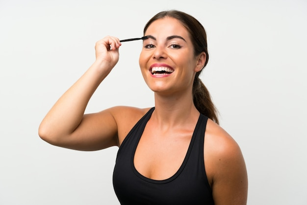 Jeune femme sur mur blanc isolé, application de mascara à la ruée cosmétique