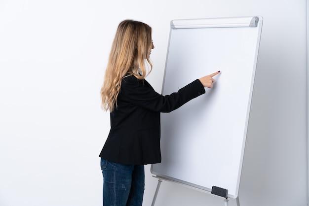 Jeune femme sur un mur blanc isolé donnant une présentation sur tableau blanc et écrit dedans