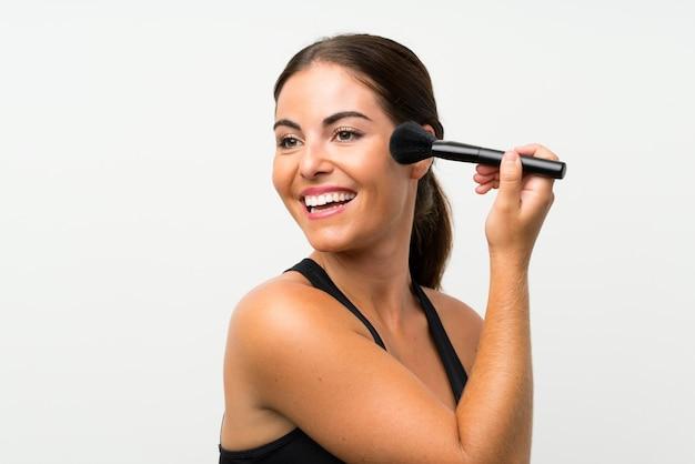 Jeune femme sur un mur blanc isolé avec pinceau de maquillage